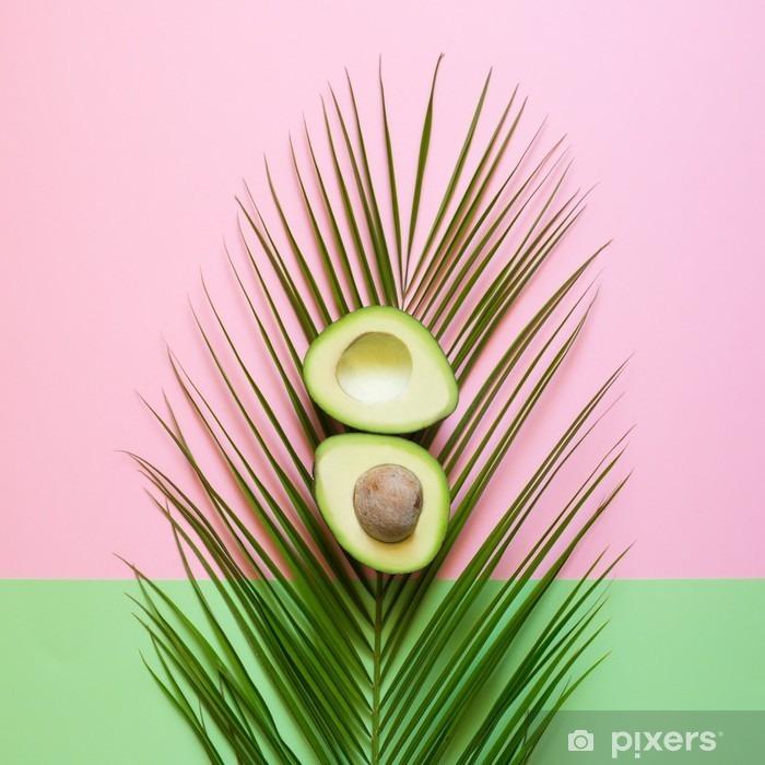 Pixerstick Sticker Rijpe avocado op palmblad op een gekleurde achtergrond. minimal-concept - Eten