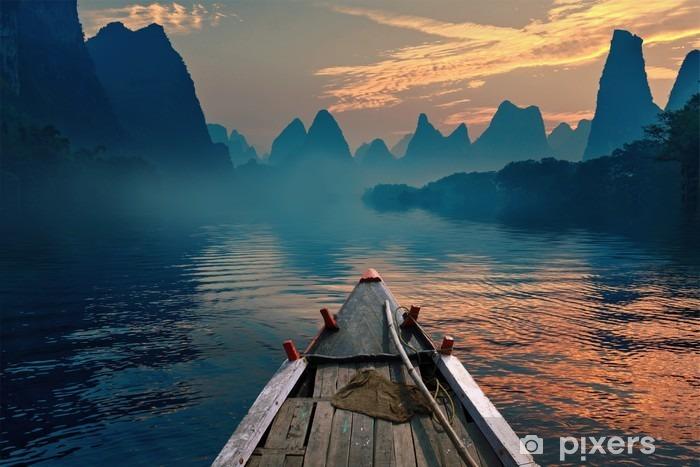Vinyl Fotobehang Een boot rijden in een rivier tijdens zonsondergang naast een mooi mount - Landschappen