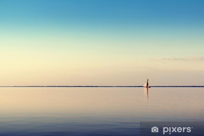 Fototapeta winylowa Woda krajobraz z białego łodzi żaglowej na spokojnych wodach w świetle zachodzącego słońca. Stonowanych i przetwarzania zdjęć. - Krajobrazy