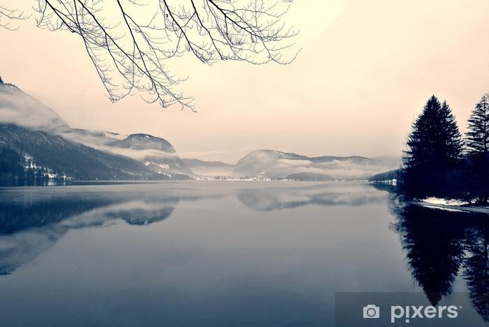 Fototapeta samoprzylepna Snowy zimowy krajobraz nad jeziorem w czerni i bieli. Obraz monochromatyczny filtrowany w stylu retro, vintage z miękki, czerwony filtr i trochę hałasu; nostalgiczna koncepcja zimowym. Jezioro Bohinj, Słowenia. - Krajobrazy