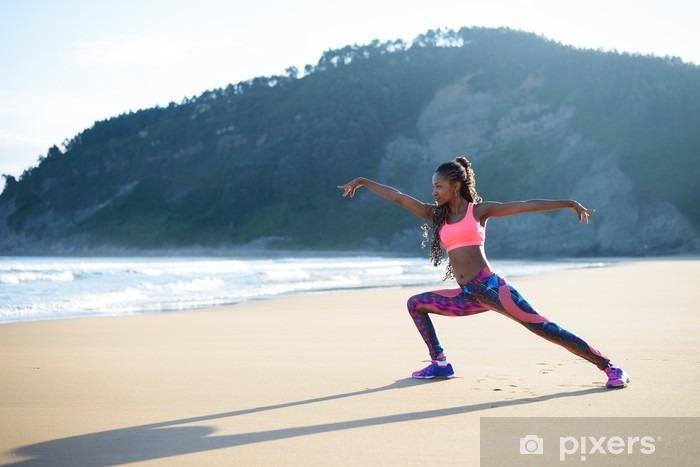 Fototapeta winylowa Kobieta fitness rozciąganie nóg i praktykujących taniec stwarza na plaży. Czarny lekkoatletka wypracowanie na zewnątrz w stosunku do morza. - Sport