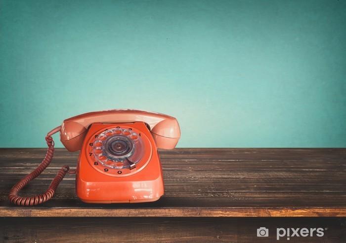 Pixerstick Sticker Oude retro rode telefoon op tafel met vintage groene pastel achtergrond -
