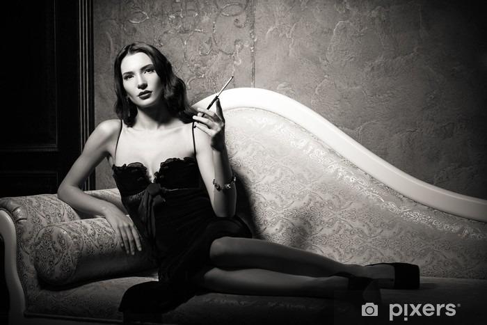 Papier peint vinyle Film noir style: élégant jeune femme allongée sur le canapé et de fumer la cigarette. Noir et blanc - Personnes