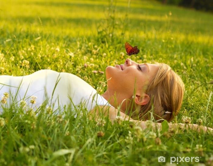 Naklejka Pixerstick Młode blond włosy kobieta leżącej na grass.Butterfly stoi na nosie. - Ludzie