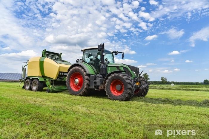 Fototapeta winylowa Ernte - traktor mit rundballenpresse im einsatz für grasssilage - Przemysł
