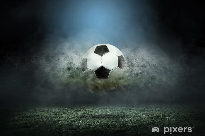 Fototapeta winylowa Poruszająca się piłka nożna wokół kropli rozchlapać na polu stadionu. - Sport