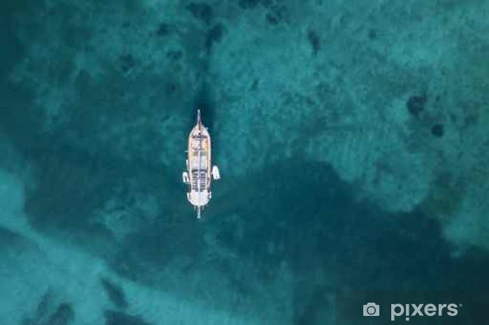 Naklejka Pixerstick Widok z lotu ptaka niewielkiego jachtu na wspaniałej plaży z turkusowym i przezroczystym morzem. Emerald Coast, Sardynia, Włochy. - Podróż
