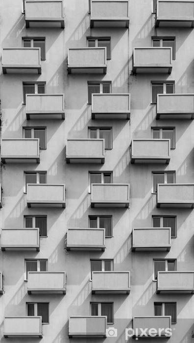 Pixerstick Sticker Een gebouw met identieke balkons en ramen met een schaduw op de muur - Gebouwen en Architectuur