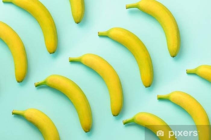 Värikäs hedelmä kuvio. banaanit yli sinisen taustan. ylhäältä. pop-art-suunnittelu, luova kesäkonsepti. minimaalinen tasainen makuyyli. Pixerstick tarra - Ruoka