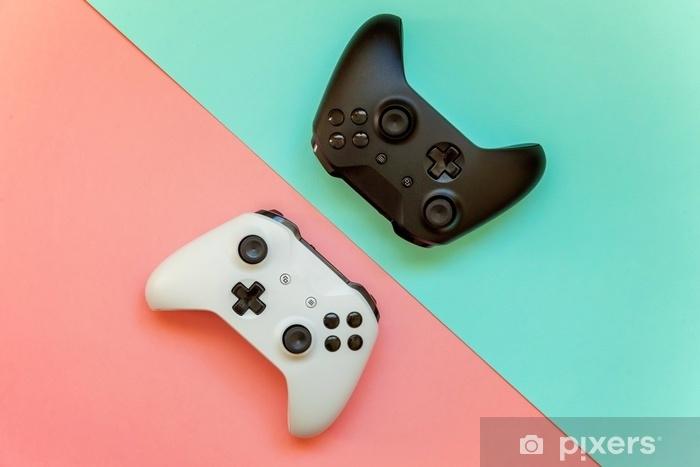 Vinyl Fotobehang Wit en zwart twee joystick gamepad, game console op roze en blauwe kleurrijke trendy moderne mode pin-up achtergrond. computer gaming concurrentie videogame controle confrontatie concept - Hobby's en Vrije tijd