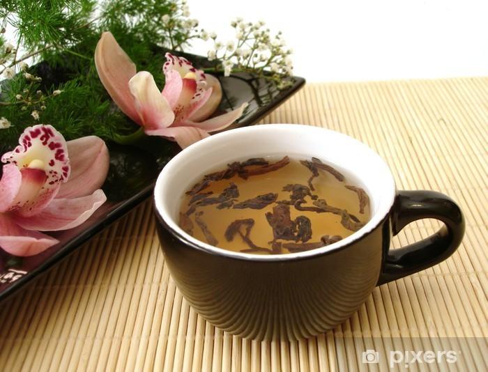 Fototapeta winylowa Kubek herbaty z różowym orchidee na czarnej płycie ponad słomy matt - Posiłki