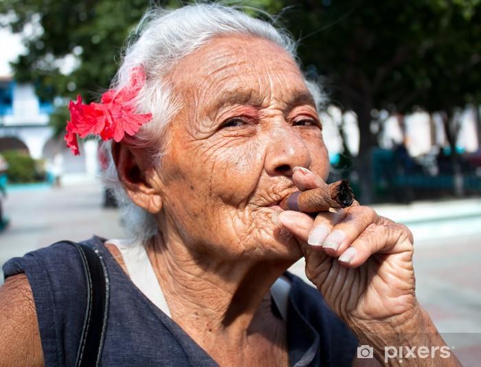 Fototapeta winylowa Stara pomarszczona kobieta z czerwonym kwiatem palenia cygara - Ameryka