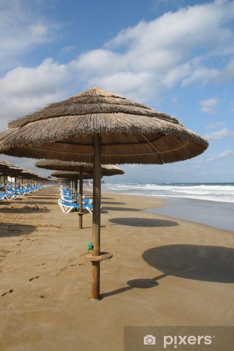 Fototapeta winylowa Wakacje w ostatni: parasole ze słomy na piaszczystej plaży - Wakacje