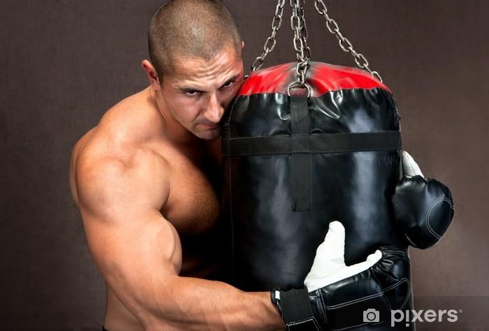 Fototapeta winylowa Athletic młody człowiek trening kickboxingu za pomocą czarnej workiem treningowym - Tematy