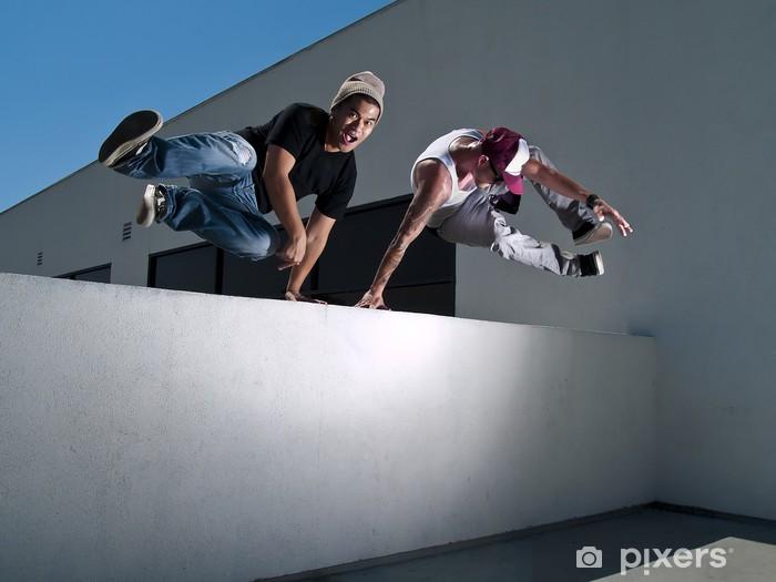 Fototapeta winylowa Dwóch mężczyzn parkour darmowe biegacze przeskakując mur - Tematy
