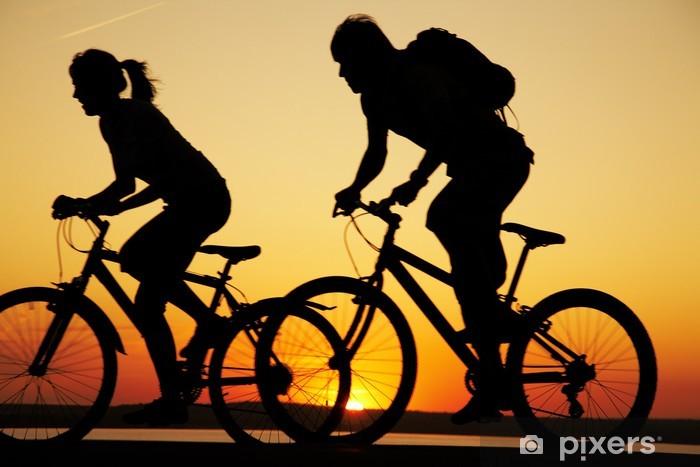 Vinilo Pixerstick Pareja joven en bicicleta al atardecer. - Ciclismo