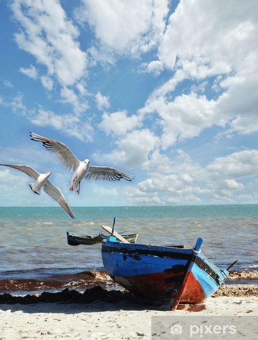 Fototapeta winylowa Wakacyjne wspomnienia: plaża z łodzi rybackiej oraz mewy - Tematy