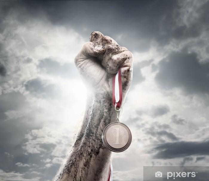 Papier peint vinyle Male hand holding médaille d'or contre le ciel dramatique - Réussite