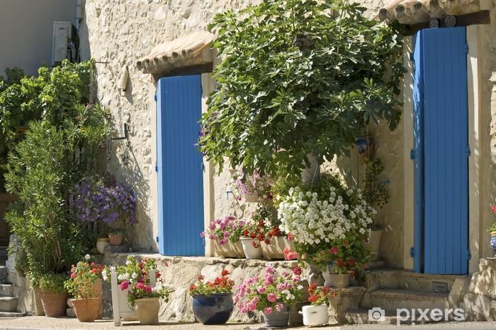 Fototapeta winylowa Domek, niebieskie drzwi z kwiatem w Provence, Francja. - Europa
