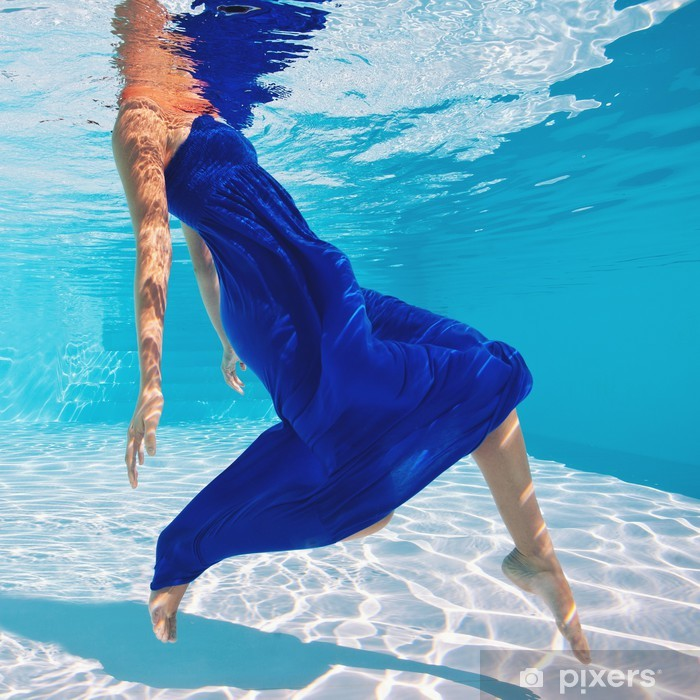 Papier peint vinyle Portrait de femme sous l'eau avec une robe bleue dans la piscine. - Vacances