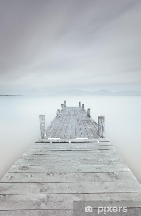 Vinilo para Nevera Muelle de madera en el lago en un ambiente nublado y brumoso. -