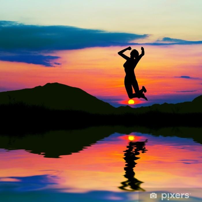 Plakat Sylwetka szczęśliwa kobieta skaczą z radości na zachód słońca. - Sporty indywidualne