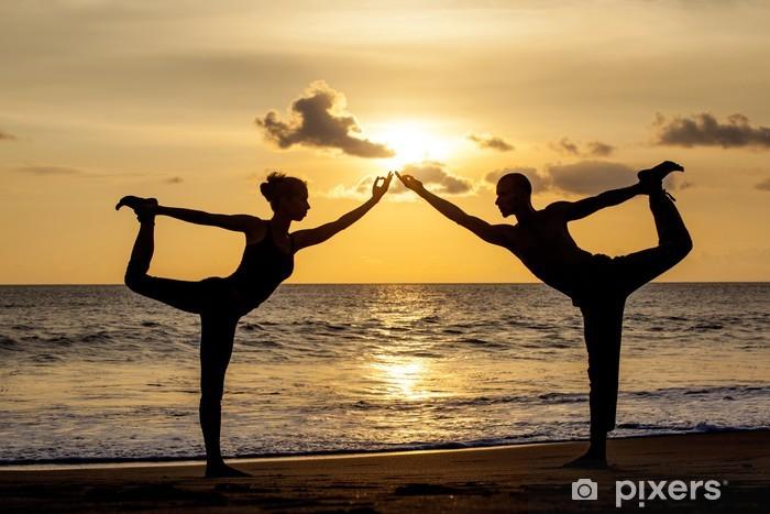 Vinilo Pixerstick Pareja haciendo ejercicios de yoga juntos estiramiento mientras la puesta de sol - Salud