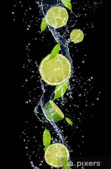 Sticker Pixerstick Limes dans les projections d'eau, isolé sur fond noir -