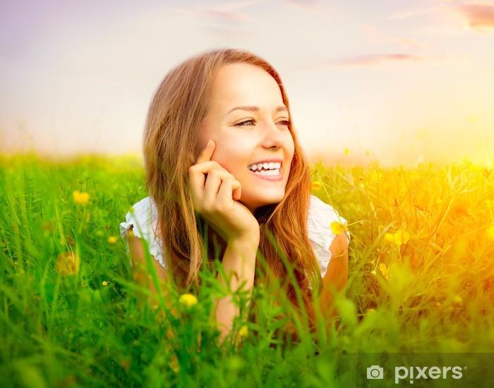 Naklejka Pixerstick Piękna Dziewczyna na łące leży na zielonej trawie - Kobiety