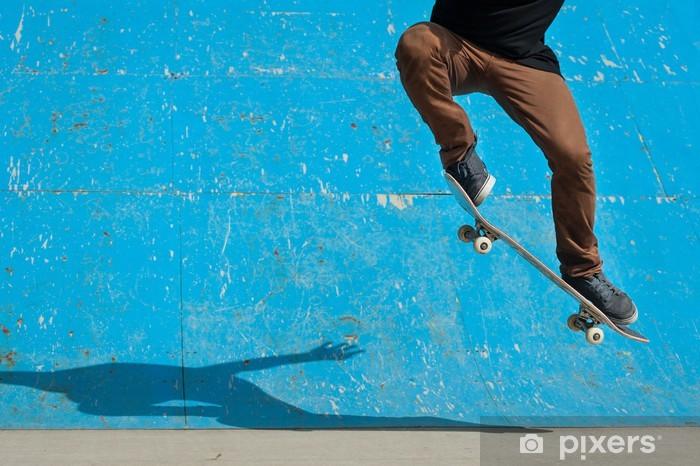 Afwasbaar Fotobehang Skateboarder doet een skateboard trick - ollie - bij skate park. - Skateboarding