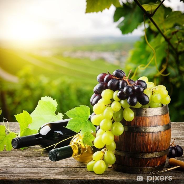 Papier peint vinyle Bouteilles de vin rouge et blanc avec des raisins frais - France