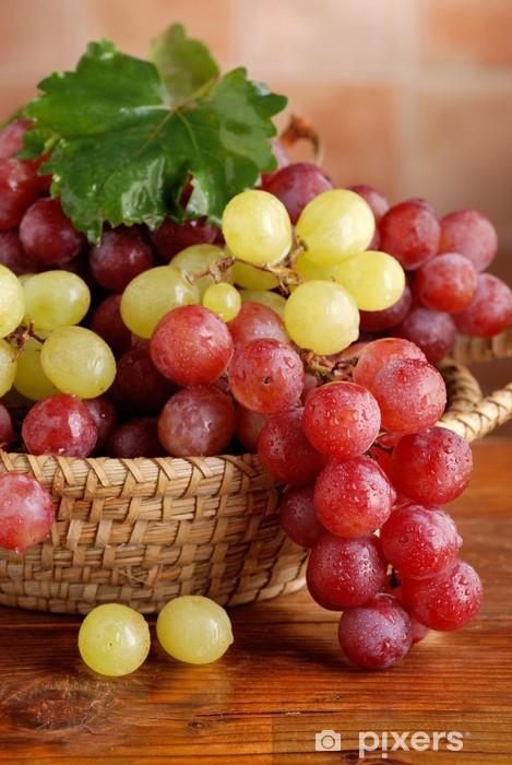Fototapeta winylowa Skupiska czarnych i białych winogron w koszu - Owoce