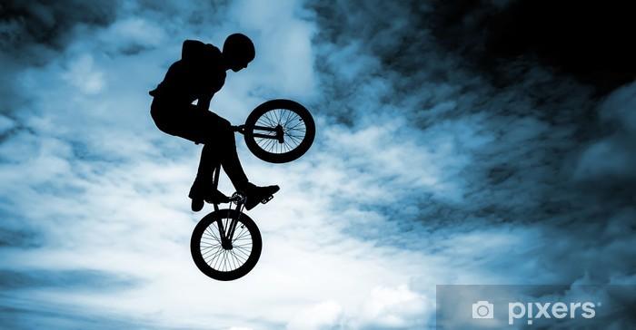 Fototapeta winylowa Człowiek robi skok z bmx rower na niebieskim tle nieba. -