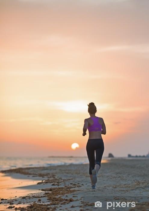 Sticker Pixerstick Fitness jeune femme courant sur la plage le soir. vue arrière - Thèmes