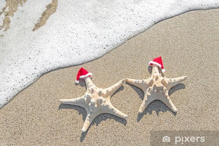 Fototapeta winylowa Morze gwiazd para w Santa kapelusze na piasku. - Święta międzynarodowe