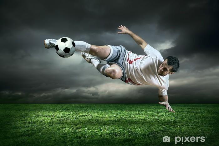 Vinyl Fotobehang Football-speler met bal in actie onder regen buiten - Thema's