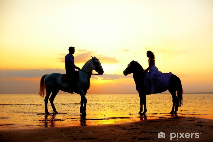 Mural de Parede em Vinil Two riders on horseback at sunset on the beach. Lovers ride hors - Casais
