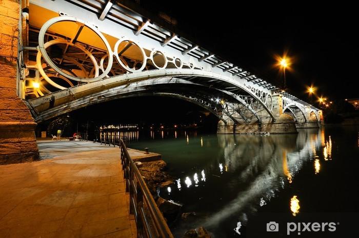 Papier peint vinyle Pont de Triana sur le fleuve Guadalquivir au coucher du soleil avec des refle de la rivière - Europe