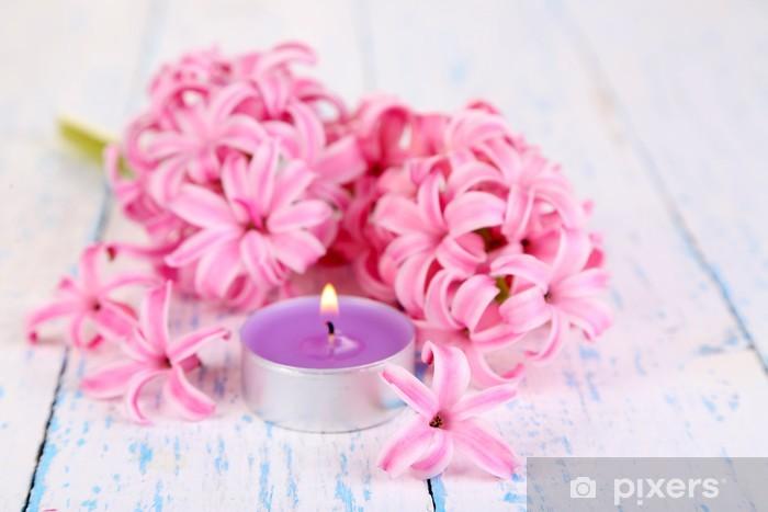 Fototapeta winylowa Różowy hiacynt z świeczka na tle drewniane - Kwiaty
