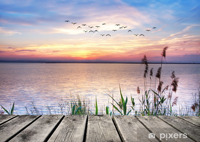 Fototapeta winylowa Drewniany pomost na tle zachodzącego słońca -