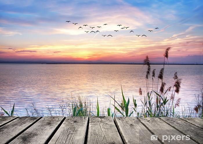 Fototapeta zmywalna Drewniany pomost na tle zachodzącego słońca -