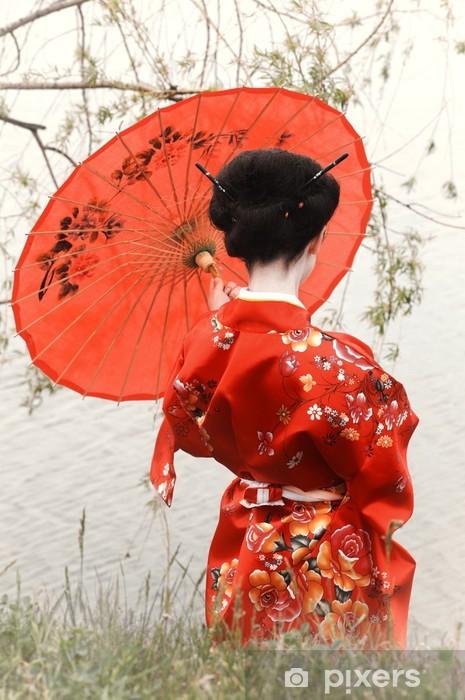 Fototapeta winylowa Gejsza z czerwonym parasolem na brzegu rzeki (widok z tyłu) - Azja
