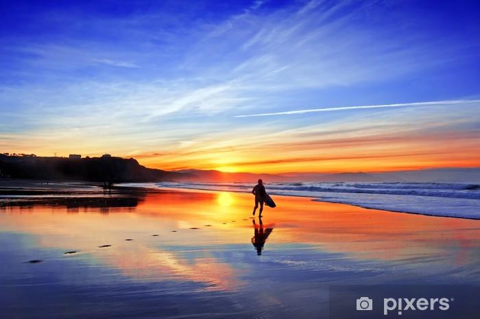 Fototapeta winylowa Surfer w plaży o zachodzie słońca - Tematy