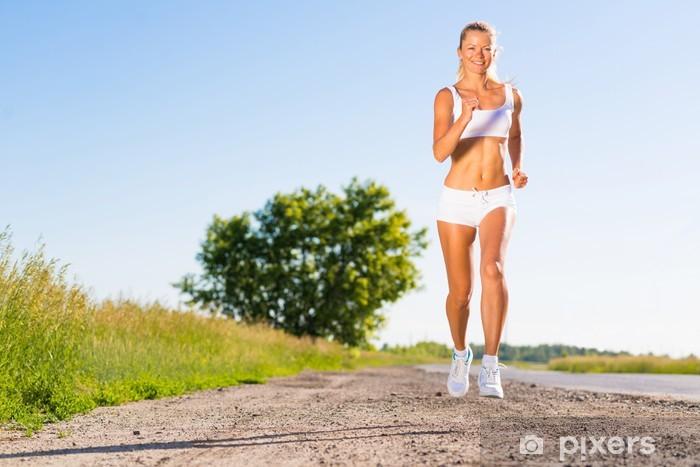Naklejka Pixerstick Młoda kobieta sportowiec działa na drodze - Tematy