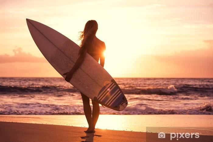 Fototapeta winylowa Sylwetka surfer girl na plaży o zachodzie słońca - Wakacje
