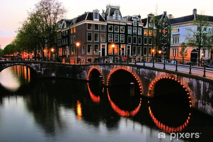 Fototapeta winylowa Słynnych kanałach Amsterdamu oświetlone na zmierzchu, Holandia - Miasta europejskie