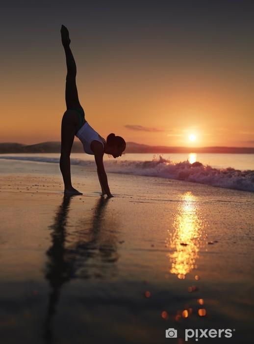 Vinilo Pixerstick Una mujer haciendo una sesión de ejercicios de yoga en la playa durante una salida del sol - Salud
