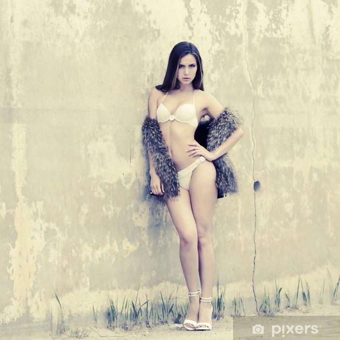 Vinyl Fotobehang Slank meisje in bikini poseren op een achtergrond van getextureerde oude muur - Thema's