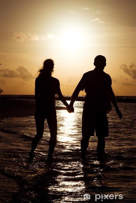 Fototapeta winylowa Sylwetka młodej pary na zachodzie słońca w pobliżu brzegu Océ - Wakacje