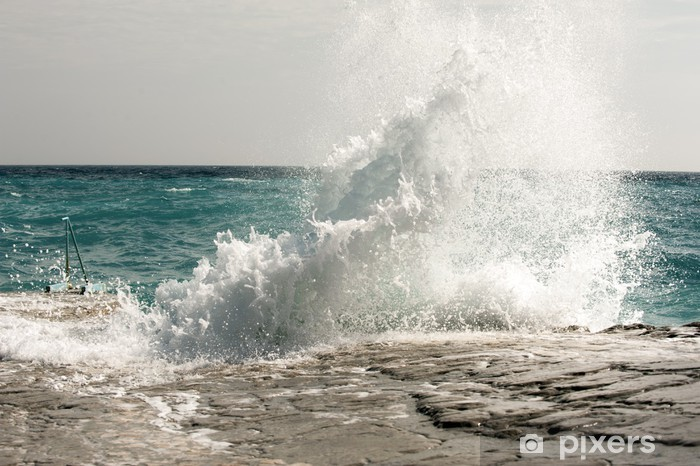 Fototapeta winylowa Załamujące się fale na plaży kamieniste, tworząc aerozol - Woda